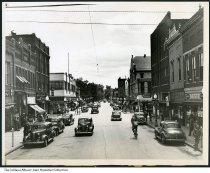 """Image of Businesses in downtown Elwood, Indiana, 1940 - Seen are Wilson & Moore shop, a shoe shine and repair store, a bank, Leeson's, a Standard service station, Royal Garment Cleaners, a drugstore, Venus Beauty Shop, signs for Rexall Drugs, Commons Walgreen System Drugs, a Kroger grocery store, and Steck's Clothing and Shoes.  This photo is stamped """"Elwood, Indiana"""" and """"July 2, 1940"""" on the back. A faint stamp crediting """"Wide World Photos, Inc."""" can also be seen."""