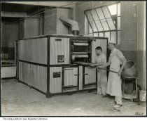 Image of City Bakery, Indianapolis, Indiana, ca. 1940 - Two bakers remove loaves of bread from a large commercial oven.