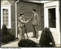 """Image of Mayor John W. Kern, Jr. at Beautility Home opening celebration, Indianapolis, Indiana, 1935 - Written on the back is """"1935 Beautility Home opening celebration / Mayor Kern  [John Worth Kern, Jr. (1900-1971)] / President Home Builders Norris P. Shelly."""" One of the men is using crutches."""