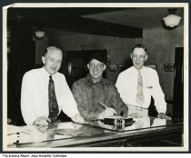 """Image of Three men at the Tavern Hotel front desk, Lake Wawasee, Indiana, 1940 - Written on the back is """"Tavern Hotel / Lake Wawasee / June 21-23 - 1940."""" The man on the right may be F. L. Palmer."""