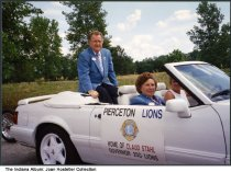 "Image of Claud Stahl in a parade car with Pierceton Lions sign, Pierceton, Indiana, 1993 - Written on the back is ""Aug. 8, 1993. Claud Stahl district Governor  of 25 G., 65 yrs. Wife Betty Rose 66 yrs., driver from Ford dealers."""