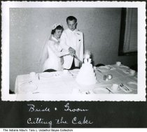 Image of The Uebelhor wedding reception, Ferdinand, Indiana, 1954 - This image shows Jo Ann Lubbers and Ronald Uebelhor cutting the cake at their wedding reception at the Daughters of Isabella (D of I) Hall in Ferdinand.