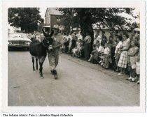 """Image of Albert Lubbers with a mule in the centennial parade, St. Henry, Dubois County, Indiana, 1962 - A crowd watching a parade. Labeled: """"Albert Lubbers leading St. Henry centennial parade, Sept 15 -1962."""""""