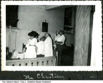 Image of Arlita Reisch and children at a christening, Indiana, ca. 1965 - A group of people are seen inside a church at a baptism.