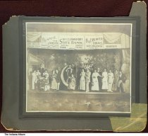 "Image of Performers on stage at the Opera House, Williamsport, Indiana, ca. 1910 - On the back is written ""Home talent play in Wmsport at Opera House called 'Crescent Moon.'"". The participants are numbered and identified as: ""1. Ione Smith 2. Hazel Dennis 3. Leonard Etmire 4. Edith Keistes 5. Karl Butt 6. Shirley Fox 7. Lelia DeMotte 8. John De Mott 9. Bonnie Cheak 10. Claud Rogers 11. Arch McKinney 12. Director 13. Dollie Kinsell 15. Bertha Stinesfaring 16. Elvin Farmer 17. June Ford 18. Tom Powell 19. Flora Ditcher (Pitcher?) 20. Pearl Dennis 21. Gertrude Dennis 22. Elwyn Williams, son of Pres. minister. 