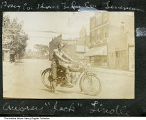 "Image of Jack Lindle on a motorcycle, Mount Vernon, Indiana, ca. 1932 - The caption reads ""Posey Co. Home Tel.(ephone) Co. Lineman - Aubrey 'Jack' Lindle."" Several businesses are seen in the background."