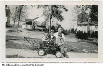 Image of Man and 3 children in a wagon, Crown Point, Indiana, 1950 - On the back, James Bock (age 30) is identified as the man on the right; the children are the Gilloglys: (L to R) Jerry (age 4 1/2), Jenny (age 2), and Bobby (age 5).    The house seen here was located across the street from the Bock Home.