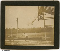 """Image of A high-diving horse by a photographer from Indianapolis, Indiana, ca. 1900 - Several people watch an animal trainer direct a horse to dive from a high platform into a pit filled with water.  The caption reads """"Queen Making her Famous Dive. Photo by Lon Burton, Indpls. [Indianapolis]""""."""