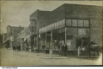 Image of Pedestrians on North 3rd Street, Ambia, Indiana, 1909 - Brick buildings on North 3rd Street in Ambia. A sign for the LaMont Brothers circus show on Friday, September 17 [1909, according to a perpetual calendar] is in the window of what appears to be a grocery store with canned goods stacked in the front window. Signs also visible for rooms for rent at 25, 23, and 50 cents, and a harness shop. A church steeple is in the background.