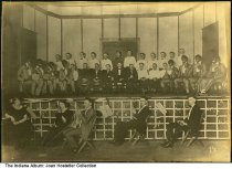 Image of Musicians and a minstrel show, Indianapolis, Indiana, ca. 1920 - A group of men are seated on the stage, eight of whom are in blackface and appear to be part of a minstrel show. Five musicians are seated on the floor in front of the stage.   There is an embossed label on the back for Tyman Bros. Photographers of Indianapolis.