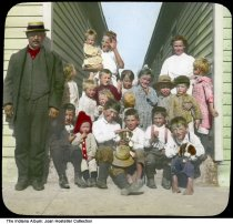 """Image of Children by Community Houses, Gary, Indiana, ca. 1915 - This lantern slide has a handwritten label """"Polish children at the Entrance of two Community Houses, Gary, Indiana."""" Gary was founded in 1906 and named for Elbert H. Gary, chairman of the board of U.S. Steel. Many Southern and Eastern European immigrants came to the area and assimilated to American society in settlement houses.  This image may show the Neighborhood House, Gary's first settlement house. It was founded by the Indiana Presbyterian Synod and the Home Mission Committee in 1909 and operated until 1973. Other settlement houses that formed by World War I include the Campbell House and Friendship House."""