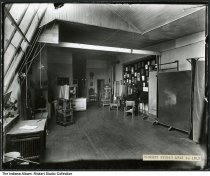 """Image of Rickert Studio interior, Huntington, Indiana, ca. 1915 - Operating room of the Rickert Studio depicting the skylight, two large format cameras on a portable stands, children's posing chairs, and backdrops. Photograph samples are displayed on the wall. A typed label reads """"Rickert Studio 1912 to 1919."""" The other end of the room is seen in image ia-0001-c018-0003."""