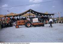 Image of Farm equipment demonstration at the Wabash County Fair, Wabash, Indiana, ca. 1960 - A crowd watches a man operating an Allis Chalmers tractor and plow.