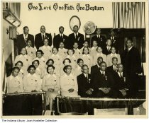 "Image of African-American church group, possibly Indianapolis, Indiana, ca. 1945 - A group of 35 men and women are inside a church with a pipe organ in the background. The sign on the back wall reads ""One Lord, One Faith, One Baptism."""