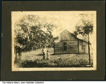 """Image of A woman and girl by a small rural cabin, possibly Birdseye, Indiana, ca. 1910 - Stamped """"James H. Kendall"""" on the back.  Part of a collection of photos from the Kendall family of Birdseye, Indiana."""