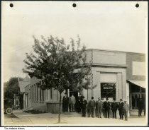 """Image of 10 Men in front of Paoli State Bank, Paoli, Indiana, 1919 - A sign for the Salvation Army is seen in the bank window; it may read """"A man may be down, but he is never out!"""" Signs on the left behind the bank read """"Hack Line Office"""" and """"Coal.""""  The building was constructed in 1912 but failed toward the end of the Depression in 1934. The town hall operated from this building on the square until 1958 and in more recent years was used as a law office.  At the far right, another man dressed in black stands in front of a sweets shop with banners showing images of ice cream fountain creations. A box in the window appears to read """"Cream Peanut Clusters."""""""
