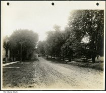 Image of Cars on a residential street with dirt road, Paoli, Indiana, 1919 - This image was part of a series of images of Paoli that included a view of the Mineral Springs Hotel.