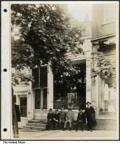"Image of Men in front of the Orange County Bank, Paoli, Indiana, 1919 - Six men are seen in front of the Orange County Bank. A Salvation Army poster in the window reads ""A man may be down, but he's never out."" The poster has the date of May 19-26, 1919. A jewelry store is next to the bank on the left.A white article of clothing hangs in the window, as does a sign for Munsing underwear and the same Salvation Army quote as in the bank window. 