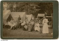 "Image of Women working in campsite, possibly near Newport, Indiana, ca. 1890 - Five women, a pre-teen girl, and a boy are seen in front of several tents in a wooded camping site. The women are at work sweeping, washing dishes, and preparing food. The wood structure to the right filled with pails, brooms, skillets, lanterns, and coffee pots has a sign above reading ""M. Hollingsworth, Newport, Ind."" 