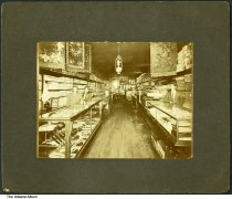 Image of Interior of a general store, Boswell, Indiana, 1903 - Three clerks are seen behind store counters holding accessories and other small items. Small area rugs and fabric are seen, and there is a sign in the back of the store for Sleepy Eye Flour.