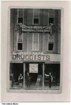 """Image of Lytle and Lytle Druggists, Delphi, Indiana, ca. 1910 - Four men stand before a three story building with signs reading """"Druge & medicines, Wholesale & Retail"""", """"Lytle and Lytle Druggists"""", and """"Lytle and Lytle for Hoosier Powder."""""""