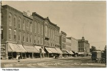 """Image of Washington Street Businesses, Delphi, Indiana, ca. 1900 - The caption reads """"Washington Street South of Franklin, Delphi, Ind."""".  Businesses signs seen are for Cafe Sharp, W. S. Margowski drugs, books, and wallpaper; Riney Bros. The Enterprise Grocery; C. O. Julius Clothier; Roach; S. H. (?) Barnes Dry Goods; and an electric shop.   Also seen in a horse cart with an umbrella marked """"(?) Summer Goods Wagons."""""""