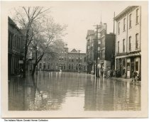 """Image of Flooded 4th Street and Pennsylvania Railroad Passenger Station, Logansport, Indiana, 1943 - Floodwaters from the nearby Wabash River. Written on the back: """"'My Hometown' / PRR Depot 1943, looking S. from 4th & Market W."""" Visible are signs for C. O. Shephard Insurance; Western Union; and Sam-Sing Hand Laundry."""