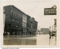 Image of Businesses under flood waters, Logansport, Indiana, 1943 - Several people are seen walking through the high water in a commercial district. Signs are seen for Greensfelder Bros. Clothing, Kinney Drugs and General Store, Todd Appliances, Kelvinator, D-X and Shell gas stations, Standard Service, Nicklas (?) Ice Cream and Candy, (Fi?)negin Hardware, and Recre(ation?) Parl(or).