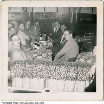 Image of Group of men in bar, Indianapolis, Indiana, ca. 1955 - Group of men drinking beer and smoking at bar tables in an unidentified tavern, probably in Indianapolis. Included are Kent Emry (on the right) and James E. Lingenfelter, Sr. Performing that night was blues singer Ophelia Hoy [see images ia-0218-0002 and ia-0218-0003].   She was known to have performed regularly at the Brass Rail, Town and Country Lounge, and the Playhouse Bar.