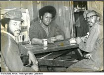 """Image of Department of Public Works employees at lunch, Indianapolis, Indiana, 1976 - Three African-American men in work clothes seated at a picnic table in front of a cigarette machine. The man in the middle wears an Afro. A note with the photographs reads """"Indpls Dept of Public Works workers at lunch time Jan 1976 / Charles Baynham is man w/ glasses & hat sitting at table on right & in center of photo w/ the lunch wagon (AKA 'roach coach')."""""""