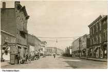 """Image of South Perry Street business district,  Attica, Indiana, 1913 - View looking northeast on South Perry Street from near the intersection of Jackson Street. Seen are the Judy Auto Company and Garage, C. W. Power, New Ideal Cafe (J. R. Phipps), Ziegler's Carpet House, George N. [M.?] Foster, and the Metropolitan. In the foreground, men pump gasoline into an early car from a curbside gasoline shed. Other automobiles are visible, as well as horse carriages and pedestrians.   Written on the back, in part, is """"Attica, Ind. / Perry St. / 11/2/13"""""""