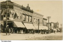 Image of Businesses on 2nd Street, Veedersburg, Indiana, ca. 1913 - Businesses in the Alabama Block include a dentist, a bank, and a clothing store. Other shops are a dry goods store, a meat market,  a barber shop, and a restaurany and bakery.