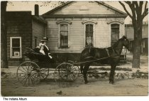 "Image of A woman and a child in a horse carriage, possibly Wanatah, Indiana, ca. 1910 - There is a photo of a horse in a store window on the left; it may read ""Wanatah"" on it. Handwritten on the back is ""poss. Wanatah, Ind."""