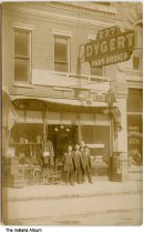 """Image of Men in front of Dygert Pawn Broker, Fort Wayne, Indiana, ca. 1920 - Three men stand in front of a store with a neon sign that reads """"Dygert Pawn Broker - 227"""", owned by William W. Wygert (b. about 1882). Next door at 229 East Main Street, a woman is seen in the window of Gustav Schubert's Dyeing and Dry Cleaning."""