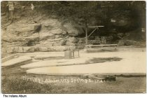 Image of Couple on a hill near sulphur spring waters, Trinity Springs, Indiana, ca. 1919 - Dated August 10, 1919. A man and a woman are seen climbing hill near signs for Shoals Community Chautauqua and Old Settlers Day. The rocks on the hill are covered in graffiti.