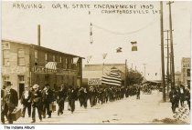 """Image of G. A. R. State Encampment attendees, Crawfordsville, Indiana, 1909 - A number of middle-aged and elderly men are seen arriving for the Grand Army of the Republic Encampment. One group marches with a sign that reads """"Tippecanoe Post No. 51 G. A. R. Monticello"""".  The group is walking past the Lyle & Reynolds Founders and Machinists building and Mercer-Winchel Timber Company."""