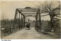 Image of Wagon on bridge over Raccoon Creek, Ladoga, Indiana, ca. 1910 - Postmarked August 26, 1910. A man in a wagon is seen crossing the bridge. A sign advertising Swift's Pure Fertilizers for sale at Gill's (?) is seen on the right.