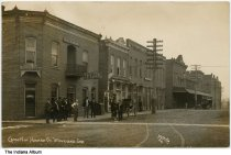 """Image of Businesses on Cross Street, Waveland, Indiana, ca. 1910 - The caption reads """"Cross N. of Howard St., Waveland, Ind."""" Businesses include the Hotel Waveland and an Indiana Bell office. Twelve men are seen near the hotel."""