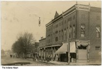Image of Businesses on the north side of the Square, Orleans, Indiana, ca. 1909 - A group of people are standing in front of J. A. Cloud store that advertised clothing and linoleum. Postmarked February 20, 1909.