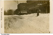 """Image of Man shoveling snow in front of stores, Rockville, Indiana, 1914 - Dated February 24, 1914. A man holding a snow shovel in in front of stores with signs that read """"Geo. Howell"""", """"Stevenson Dry Goods"""" and """"Shoes."""" A drugstore in in the background on a corner."""