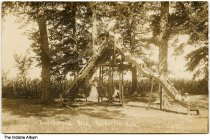 Image of Children on a playground slide at Beechwood Park, Rockville, Indiana, ca. 1917 - Postmarked October 16, 1913. A number of children are seen on a wooden slide, and a lone child is on a glider underneath the slide.