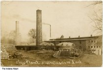 Image of Clay plant and factory, Bloomingdale, Indiana, ca. 1908 - Postmarked April 21, 1910. This postcard shows three tall smokestacks, some large kilns, and a number of neatly stacked clay items.