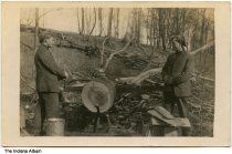 Image of Trick photo of a man sawing a log with himself, probably Parke County, Indiana, ca. 1910