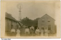 Image of Family by a house with a windmill, possibly Parke County, Indiana, ca. 1910