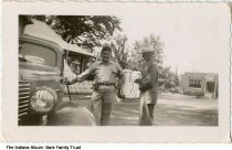"""Image of Lyle and Baxter Bare at a Helping Oil station, Anderson, Indiana, ca. 1945 -  The men are identified as Lyle E. Bare (b. 4-17-1921 in Jasonville, Indiana, d. 1-16-1999 Pendelton, Ind., married to Betty Terhune)  and W. Baxter Bare. Lyle Bare worked at Helping Oil at 8th and John Streets in Anderson.  Two gasoline pumps are seen in the background. A building on the right has a sign reading """"Harlan."""""""