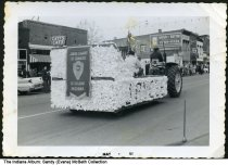 """Image of Jaycees parade float, Petersburg, Indiana, ca. 1960 - A sign on the float reads """"Junior Chamber of Commerce - Petersburg Indiana"""" and """"Jaycees."""" Timestamped May 1961. Signs are seen for Catt's Cafe and Nunn-Better Flour and Feeds."""