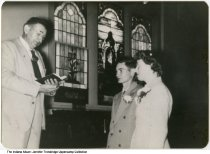 Image of James Uppencamp and Rosemary Whaley wedding, Otwell, Indiana, October, 1953 - James Ray Uppencamp (second from left) and Rosemary Whaley (right) are seen at their wedding with the clergyman who married them. A large stained glass window is in the background.