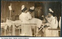 Image of Indianapolis Training School for Nurses students, Indianapolis City Hospital, Indianapolis, Indiana, ca. 1906 - Three women in nurse's uniforms pretend to perform surgery on a 4th person. The women were students at the Indianapolis Training School for Nurses at Indianapolis City Hospital; Lulu Lucinda Records is standing second from the left.