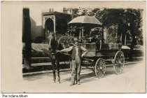 """Image of Peddler with a fruit or delivery wagon, Indiana, ca. 1910 - On the parasol above the wagon it reads """"Stag Trousers"""" and """"(Mendel?) Clothing, Lafayette, Ind."""""""