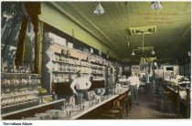 Image of Interior of Busjahn and Schneider Drugstore, Logansport, Indiana, ca. 1910 - Two men are seen inside the drugstore, one behind the soda fountain counter.